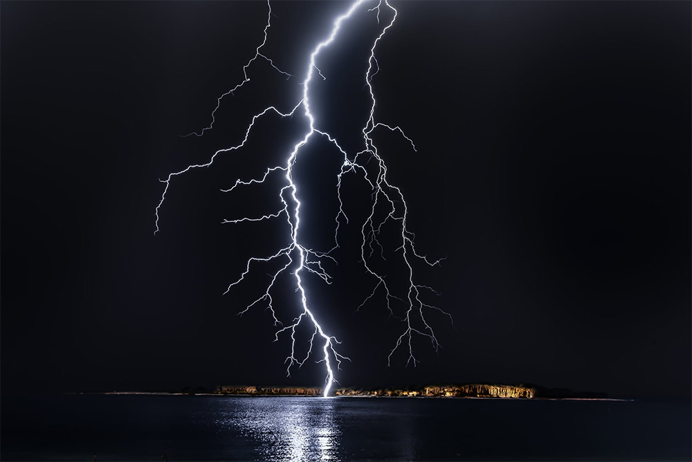 A Powerful Discharge from the Base of a Cloud to the Earth's Surface, also Known as Lightning